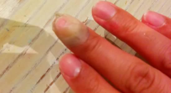 怪我をした中指に絆創膏をまいているところ
